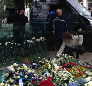 A woman places flowers for an older man, perhaps her father